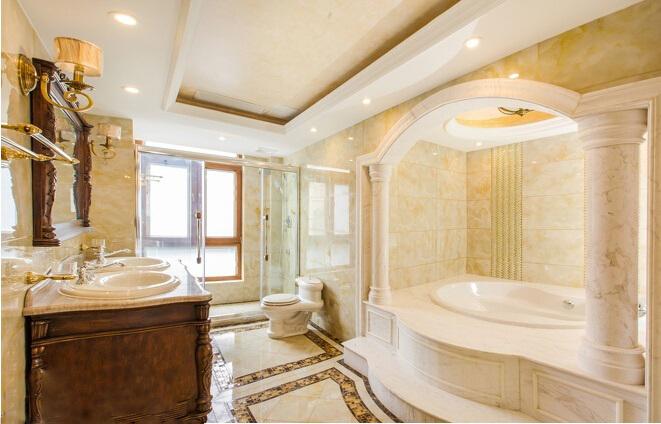 深色大理石装修效果 卫浴间的设计也非常的欧式宫廷风。雕刻着复杂浮雕的浴室柜,需要登上台阶才能踏入的白色浴池,甚至在浴池前还竖立着两根简约的罗马柱。不过卫浴间的颜色较为浅淡,墙壁铺贴选用的是德国米黄大理石,简约罗马柱则是由白色的鱼肚白大理石雕刻而成,整体感觉明亮活泼不少!